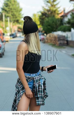 Cool young blonde woman with smart phone in the street. Hipster millennial teenage girl in black beanie, black tank top, denim shorts and plaid shirt. Mild retouch, no filter.