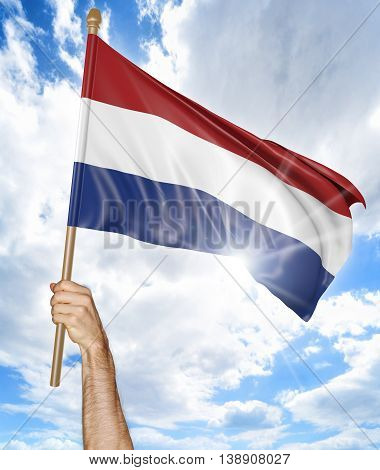 Person's hand holding the Dutch national flag and waving it in the sky, 3D rendering