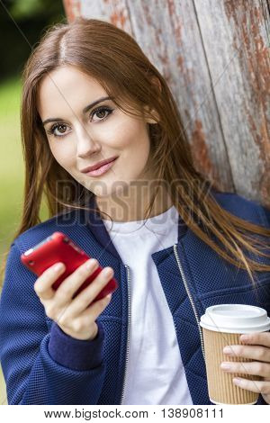 Outdoor portrait of beautiful girl or young woman with red hair texting on her mobile cell phone and drinking coffee