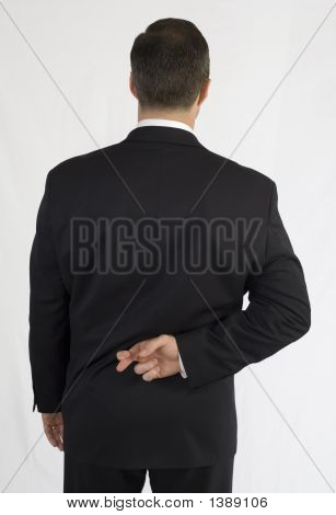 Businessman With Fingers Crossed Behind Back