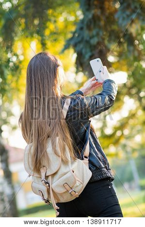 Young woman with backpack taking a selfie in park. Female student taking a self portrait of her smart phone outdoors. Rear view, unrecognizable person.