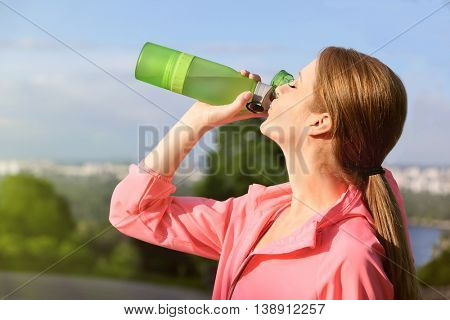 Sporty woman drinking water after jogging  on a sunny day