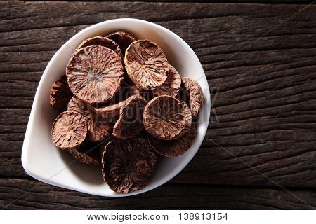 slices of dry nutmeg on the wooden background