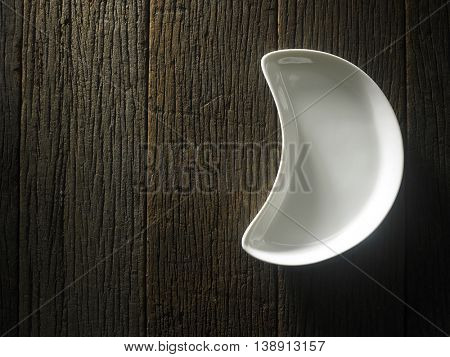 moon shape porcelain plate on the wooden background
