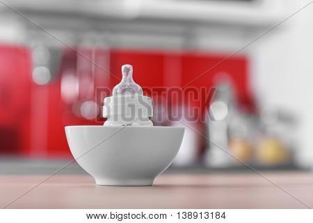 Baby bottle in bowl on kitchen table