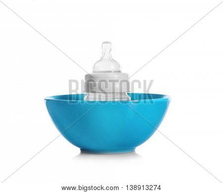 Baby bottle in bowl, isolated on white