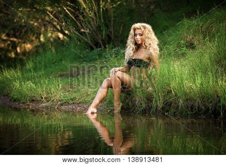 Beautiful blonde girl sitting on the shore of the lake in the green grass and trees. Natural beauty, unity with nature and ecology.