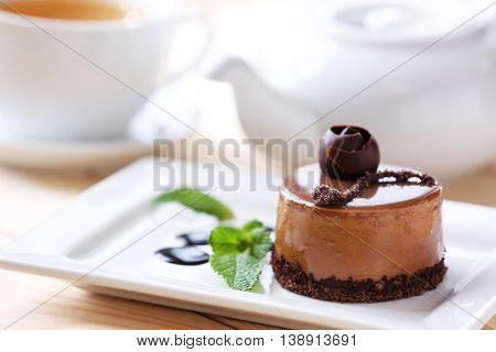 Caramel cake with tea on wooden table