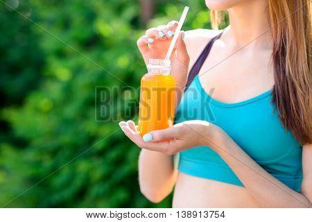 Sportswoman drinking detox juice on street