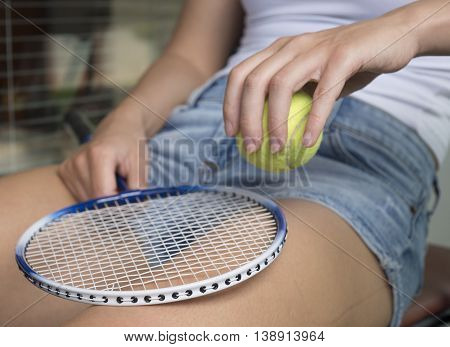 The girl in shorts with a racket and tennis ball.