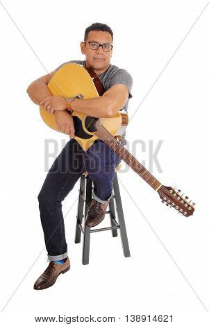 A middle age Hispanic man sitting isolated for white background holding his guitar looking into the camera.