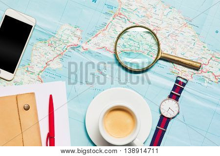 Preparation for travel concept - map, magnifying glass, cup of coffee, notepad, phone, wrist watch