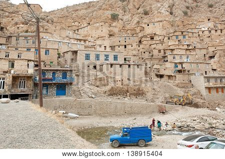 KURDISTAN, IRAN - OCT 11, 2014: Cars and villagers of small town Palangan with clay and brick houses in mountains on October 11, 2014. Islamic Republic of Iran is the world's 17th most populous nation