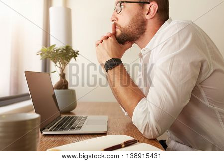 Side view of businessman sitting at his desk with a laptop and looking away. Man at his workdesk thinking of business solutions.