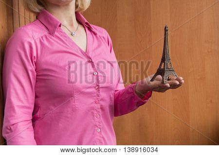A woman holding a small Eiffel tower, inviting in the journey.