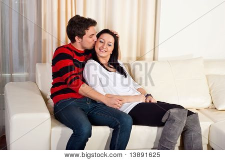 Loving Young Couple On Sofa Home