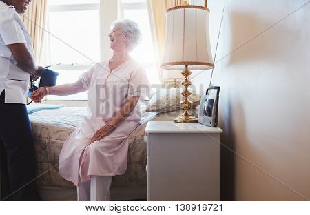 Indoors shot of happy senior woman sitting on bed with female nurse checking blood pressure. Home caregiver testing blood pressure of old woman.
