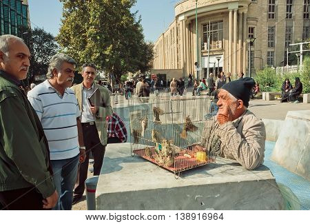 TEHRAN, IRAN - OCTOBER 25, 2014: Birdman trades the sparrows on crowded street on October 25, 2014. About 30 perc. of Iran's public-sector workforce and 45 perc. of industrial firms are located in Tehran