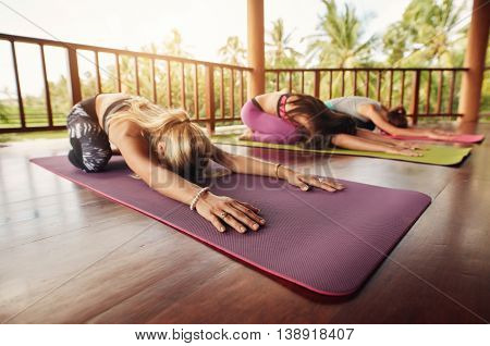 Group Of Young Women Doing Child Pose Yoga