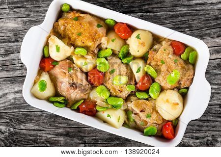 stewed chicken meat new potatoes and butter lima bean on old wooden table view from above close-up