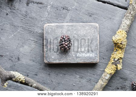 NATURAL inscription and blackberries on a wooden table.