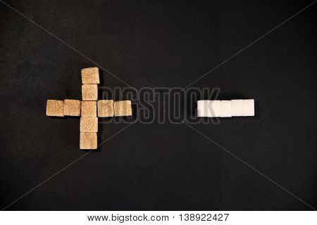 White and brown sugar cubes arranged in plus and minus figures on the black background