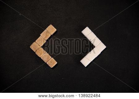 Brown and white sugar cubes arranged in triangular brackets on black background