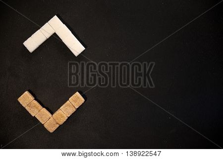 Brown and white sugar cubes arranged in triangular brackets on black background with copyspace on the right