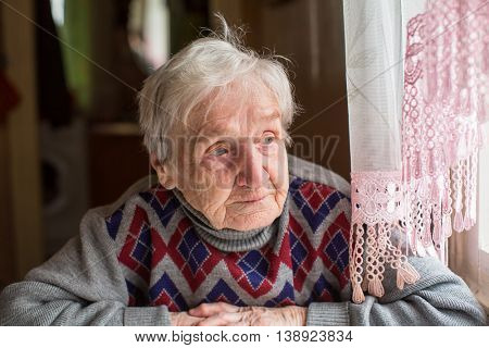 Elderly woman in a sweater looking out the window sitting at the table.