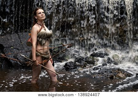 archer stands in the water with the bow and arrow