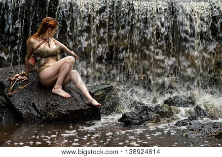 young female archer enjoys waterfall on stone outdoors