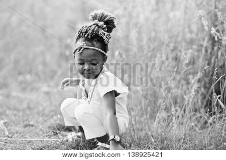 African baby girl walking at park. Black and white