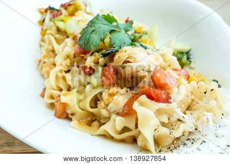 close-up of plate of pasta and chicken with lettuce