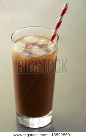 Iced coffee with straw on gray table