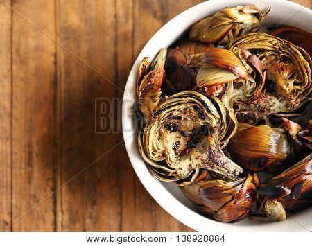 Baked artichokes with spices in a bowl on wooden background