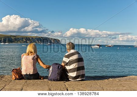 Swanage Dorset UK. July 2016. Couple sitting on the pavement overlooking Swanage bay