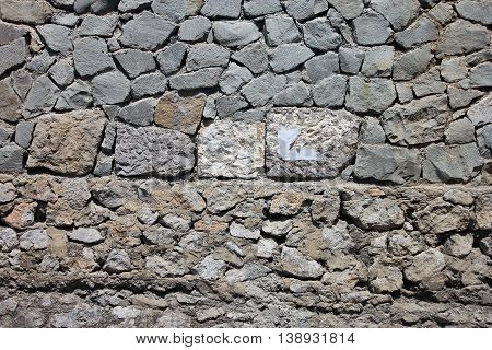 texture of old dilapidated shabby rubble masonry of wall foreground closeup