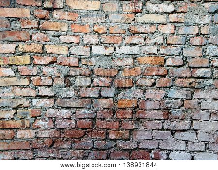 texture of old dilapidated shabby red brick masonry of red brick wall foreground closeup