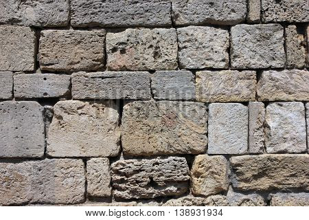 texture of old dilapidated shabby sandstone masonry of square sandstone blocks wall foreground closeup in Crimea