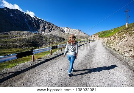 Tourist Woman Walking At The Mountains Road