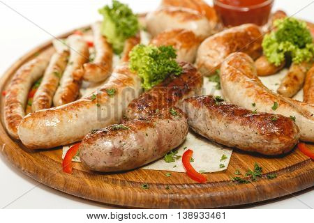 Different kind of grilled sausages on the wooden plate on white background