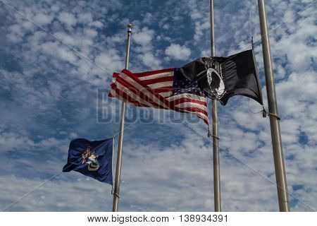 pow mia, american, and michigan flags at half staff