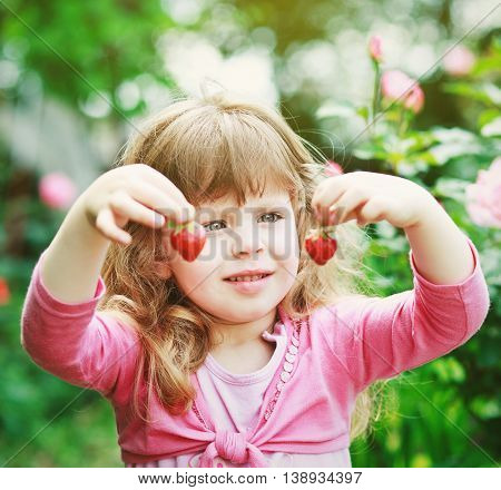 little girl play with fresh strawberries on  nature backgraund