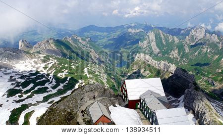 Mountain world in Switzerland, view from Säntis on the Alpstein-Massif with the Lake Seealp in Appenzellerland,  steep rocks and snow fields, in the foreground the Säntis mountain house
