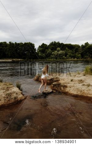 Attractive Caucasian Teen Girl Crossing From Island To Island In River Wearing White Leotards From Back