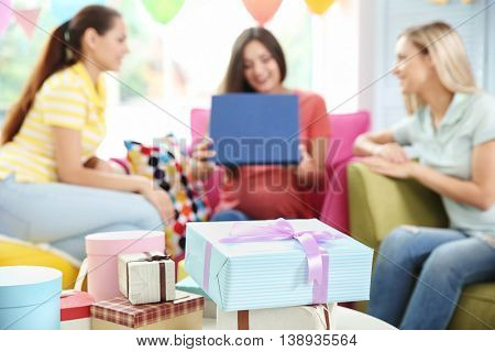 Presents and pregnant woman with friends at baby shower party