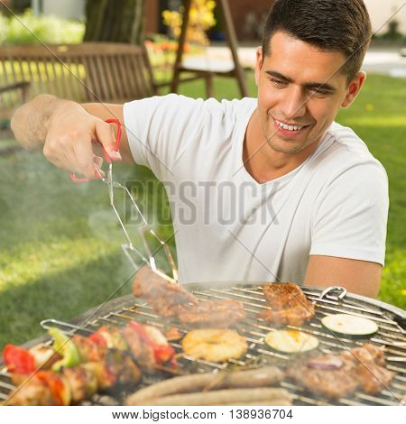 Man Preparing Grill For Friends