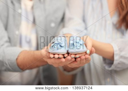 Husband and pregnant woman holding baby shoes, closeup