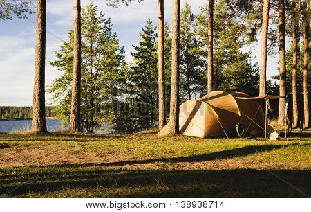 the small tent in the woods on the shores of lakes