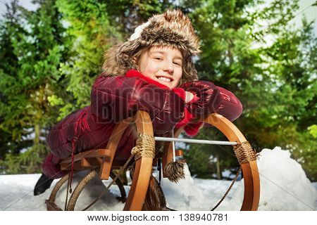 Smiling girl having fun in winter snow on a sledge at the forest